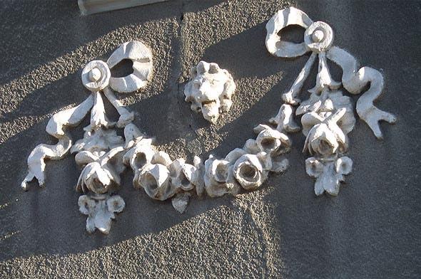 украшения фасада здания Каменные цветы и львиные морды