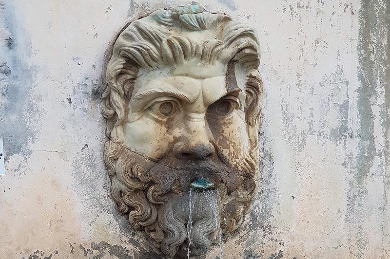 гротескное лицо украшает фонтан