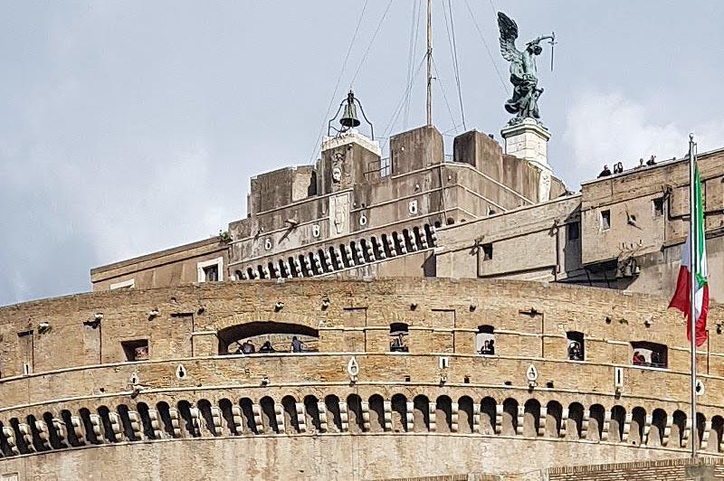 колокол милосердия возле статуи архангела михаила на вершине замка