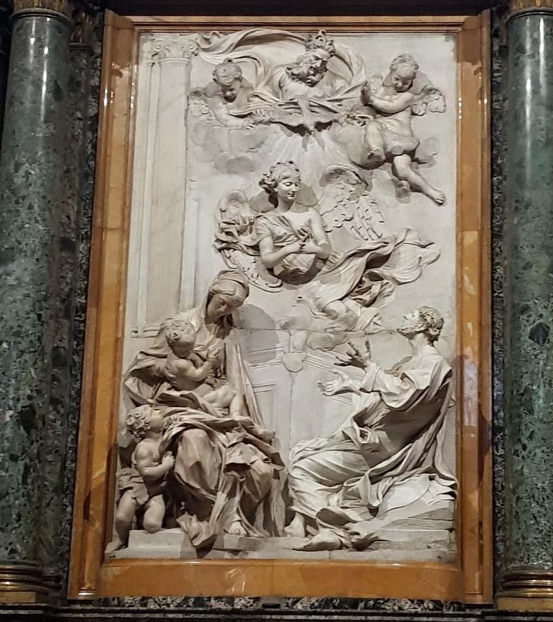 на белой плоскости алтаря скульптурное изображение ангела и святого семейства
