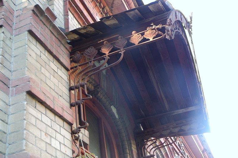 на дверном навесе застыли узоры стеблей и листьев фантастических растений